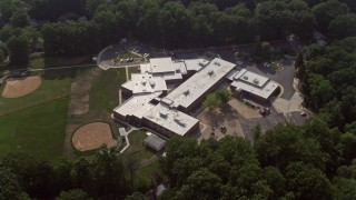 AX75_156 - 5K stock footage aerial video tilting to bird's eye view of Canterbury Woods Elementary School in Annandale, Virginia