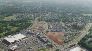 AX75_171 - 5K stock footage aerial video flying over homes and streets to approach strip mall and stores in Manassas, Virginia