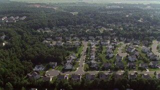 AX75_175 - 5K stock footage aerial video flying over suburban homes to approach warehouse buildings in Manassas, Virginia