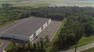 AX75_176 - 5K stock footage aerial video flying over warehouse buildings to approach hangars at Manassas Regional Airport