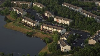 AX76_002 - 5K stock footage aerial video flying by waterfront town houses beside pond, Manassas, Virginia, sunset