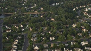 AX76_003 - 5K stock footage aerial video tilting to bird's eye view of suburban homes in Manassas, Virginia, sunset