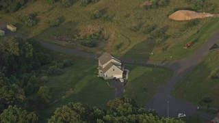 AX76_006 - 5K stock footage aerial video flying by a home, green lawns, Manassas, Virginia, sunset