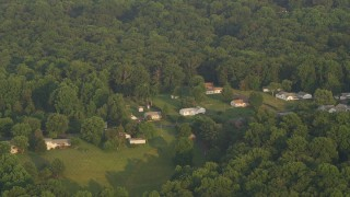 AX76_007 - 5K stock footage aerial video flying by rural homes near forest, Manassas, Virginia, sunset