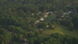 AX76_008 - 5K stock footage aerial video flying by rural homes near forest, Manassas, Virginia, sunset