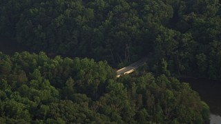 AX76_009 - 5K stock footage aerial video flying by Yates Ford Road bridge, partially hidden in forest, Clifton, Virginia, sunset