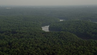 AX76_010 - 5K stock footage aerial video flying by Occoquan River winding through forest, Clifton, Virginia, sunset