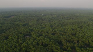 AX76_012 - 5K stock footage aerial video flying over dense forest, rural homes, Clifton, Virginia, sunset