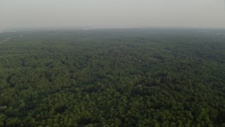 AX76_013 - 5K stock footage aerial video flying by forest, partially hidden rural homes, Clifton, Virginia, sunset