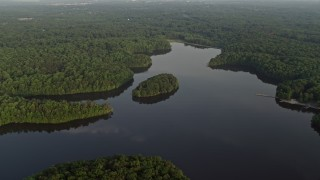 AX76_015 - 5K stock footage aerial video flying by Burke Lake, tree-covered shores, Fairfax Station, Virginia, sunset