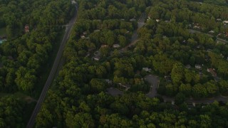AX76_018 - 5K stock footage aerial video of a bird's eye view of tree-lined suburbs, Springfield, Virginia, sunset