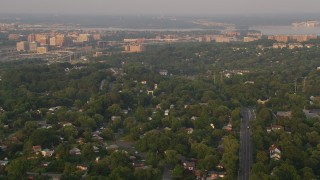 AX76_027 - 5K stock footage aerial video flying over neighborhood, approach row houses, Alexandria, Virginia, sunset