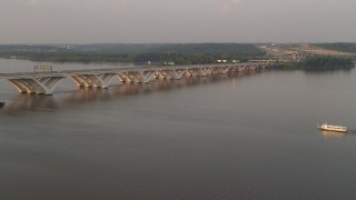 AX76_032 - 5K stock footage aerial video of ferry near Woodrow Wilson Memorial Bridge, Potomac River, Fort Washington, Maryland, sunset