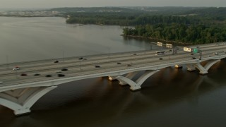 AX76_033 - 5K stock footage aerial video of cars crossing Woodrow Wilson Memorial Bridge, Potomac River, Fort Washington, Maryland, sunset