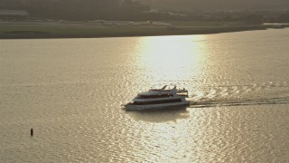 AX76_039 - 5K stock footage aerial video tracking a ferry on the Potomac River Arlington, Virginia, sunset