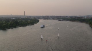 AX76_040 - 5K stock footage aerial video approaching sailboats and ferry on Washington Channel near Washington Monument, Washington D.C., sunset