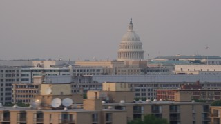 AX76_044 - 5K stock footage aerial video of the United States Capitol dome and office buildings, Washington D.C., sunset