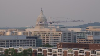 AX76_045 - 5K stock footage aerial video flying by United States Capitol dome and office buildings, Washington D.C., sunset