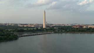 AX76_060 - 5K stock footage aerial video of Washington Monument seen from Tidal Basin, Washington D.C., sunset