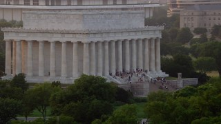 AX76_068 - 5K stock footage aerial video flying by the south side of the Lincoln Memorial with tourists, Washington D.C., sunset