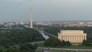 AX76_069 - 5K stock footage aerial video flying by Lincoln Memorial, revealing Reflecting Pool, Washington Monument, National Mall, Washington D.C., sunset