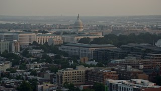 AX76_087 - 5K stock footage aerial video of the United States Capitol dome behind Senate Office Buildings, Washington D.C., sunset