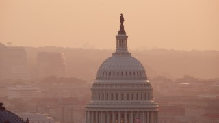 AX76_090 - 5K stock footage aerial video of the United States Capitol and Thomas Jefferson Building domes, Washington D.C., sunset