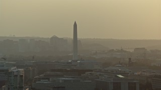 AX76_092 - 5K stock footage aerial video of the Washington Monument and office buildings in Washington D.C., sunset