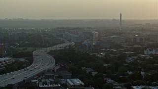 AX76_094 - 5K stock footage aerial video of Interstate 695, Capitol Power Plant, and Washington Monument, Washington D.C., sunset