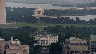 AX76_105 - 5K stock footage aerial video of the Jefferson Memorial behind the White House, reveal Washington Monument base, Washington D.C., sunset