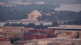 AX76_108 - 5K stock footage aerial video of The Jefferson Memorial across Tidal Basin in Washington D.C., sunset