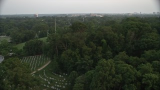 AX76_116 - 5K stock footage aerial video of gravestones and trees at Arlington National Cemetery, Virginia, twilight