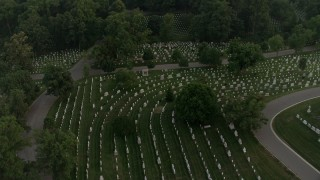AX76_118 - 5K stock footage aerial video flying over Arlington National Cemetery, tilt to gravestones, Virginia, twilight
