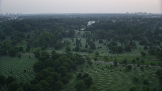 AX76_127 - 5K stock footage aerial video of rows of gravestones near Arlington House at Arlington National Cemetery, Arlington, Virginia, twilight