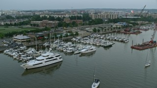 AX76_134 - 5K stock footage aerial video of Yachts docked at Gangplank Marina, Washington, D.C., twilight