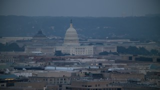 AX76_157 - 5K stock footage aerial video of the Thomas Jefferson Building and United States Capitol seen from Georgetown, Washington, D.C., twilight