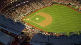 AX76_173 - 5K stock footage aerial video of a reverse view of Nationals Park during a baseball game, Washington, D.C., twilight