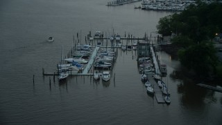 AX76_174 - 5K stock footage aerial video flying by docked boats at a marina on the Potomac River, Washington, D.C., twilight