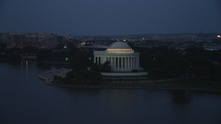 AX76_181 - 5K stock footage aerial video approaching and flying by the Jefferson Memorial lit up for evening, Washington, D.C., twilight