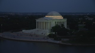 AX76_182 - 5K stock footage aerial video flying by the front of the Jefferson Memorial lit up for the night, Washington, D.C., twilight