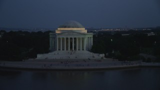 AX76_183 - 5K stock footage aerial video flying by visitors on the steps of the Jefferson Memorial, lit up for the night, Washington, D.C., twilight