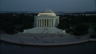 AX76_184 - 5K stock footage aerial video of the Jefferson Memorial, lit up for the night, with tourists on the steps, Washington, D.C., twilight