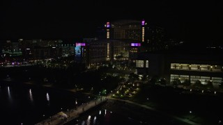 AX77_014 - 5K stock footage aerial video flying by pier and Gaylord National Resort & Convention Center, National Harbor, Maryland, night