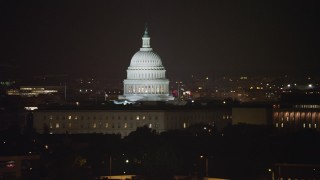 AX77_027 - 5K stock footage aerial video of the United States Capitol behind House office building and James Madison Building in Washington, D.C., night