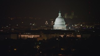 AX77_029 - 5K stock footage aerial video of United States Capitol behind Library of Congress buildings in Washington, D.C., night