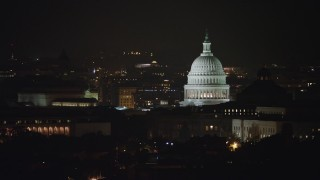 AX77_030 - 5K stock footage aerial video of the United States Capitol and Thomas Jefferson Building domes in Washington, D.C., night