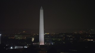 AX77_060 - 5K stock footage aerial video of Washington Monument circled by American flags, Washington, D.C., night