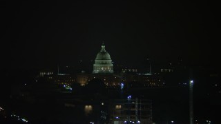AX77_069 - 5K stock footage aerial video of the United States Capitol Building behind cranes in Washington, D.C., night