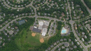 AX78_018 - 5K stock footage aerial video of a bird's eye view of Union Mill Elementary School, suburban homes, Clifton, Virginia