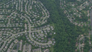 AX78_038 - 5K stock footage aerial video of a reverse view of suburban homes, reveal Great Falls Plaza in Sterling, Virginia